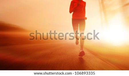 Athlete running on the road in morning sunrise training for marathon and fitness. Healthy active lifestyle, motion blur of woman exercising outdoors. copyspace. - stock photo