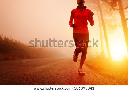 Athlete running on the road in morning sunrise training for marathon and fitness. Healthy active lifestyle latino woman exercising outdoors. Motion blur to show speed. - stock photo