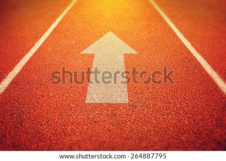 Athlete Running Track with an Arrow Pointing Forward as Motivation and Inspiration Symbol for designs or graphic posters background, Instagram Like Toned Image with Selective Focus. - stock photo