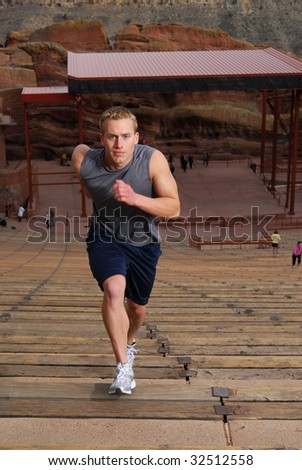 Athlete running up stairs at an outdoor amphitheater - stock photo