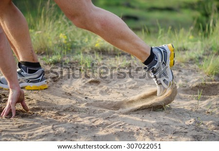 Athlete's foot in sneakers which starts to run. Sand flies under their shoes. Foot motion blur.