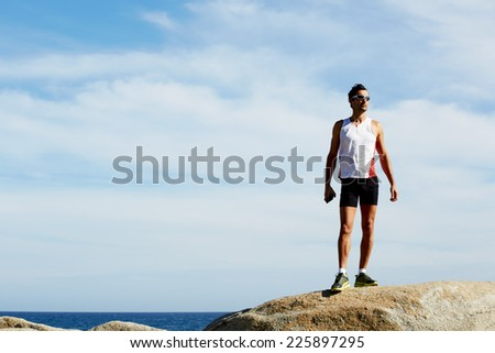 Athlete standing on sea rocks at sunny summer day while resting after intensive training outdoors, exhausted fit runner after workout resting on seaside, sportsman listening to music with headphones - stock photo