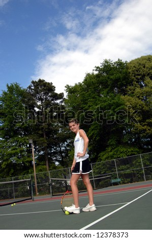 Athlete stands with her foot on a tennis ball waiting for game to start.  She is also holding her racket.  Blue sky. - stock photo