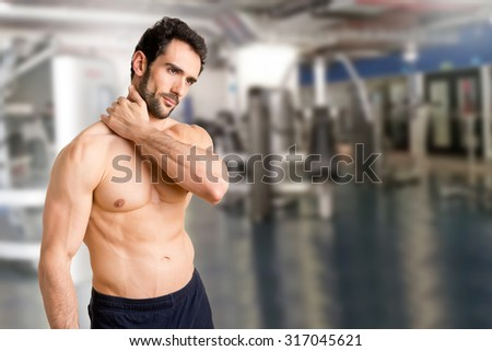Athlete suffering from neck pain in a gym - stock photo