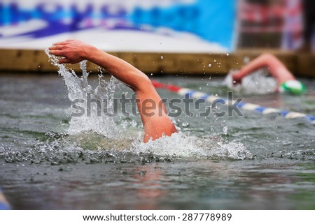 Athlete swimming in the open air pool. Shallow DOF - stock photo