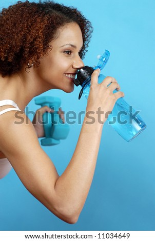 Athlete taking a break at the gym for a quick drink from her water bottle - stock photo