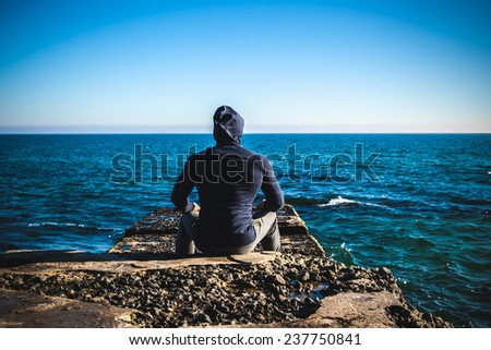 athlete taking break sitting on rocks with sea horizon  - stock photo