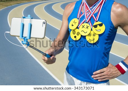 Athlete taking selfie wearing gold medals with bright yellow emoji faces with smartphone on selfie stick standing at the running track - stock photo