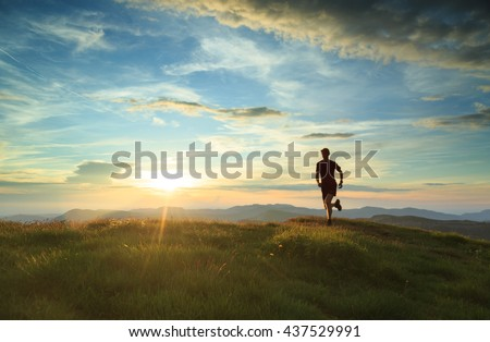 Athlete trail running in Massif du Vercors during sunset. Shallow D.O.F. and with motion blur.