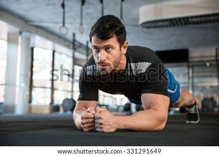 Athlete wearing blue shorts and black t-shirt making static exercise - stock photo