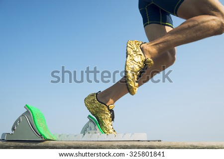 Athlete wearing gold running shoes takes off in a blur from from the race track starting blocks  - stock photo