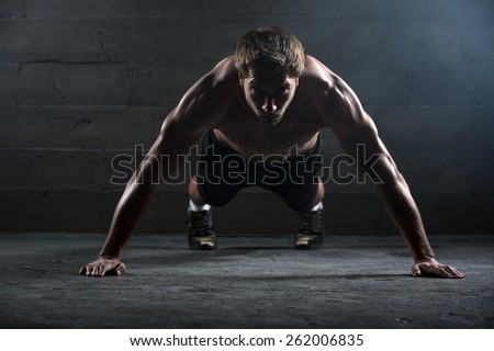 Athlete with a beautiful body and a naked torso doing push-ups exercise on the floor. Studio shot in a dark tone. - stock photo