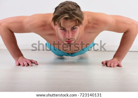 Athlete with concentrated face on white background. Man does pushups on white floor, close up. Sports and healthy lifestyle routine concept. Guy with bristle works out at gym