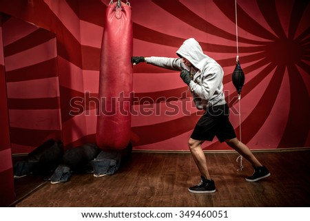 Athlete with hoody working out at boxing gym, getting ready for fight - stock photo