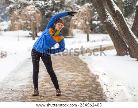 Athlete woman doing exercises during winter training outside in cold snow weather in park - stock photo