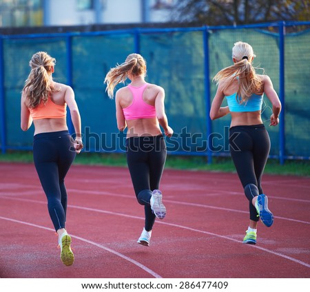 athlete woman group  running on athletics race track on soccer stadium and representing competition and leadership concept in sport - stock photo