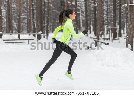 Athlete woman runner running in cold snowing weather. Cardio street training marathon jogging - stock photo