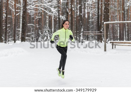 Athlete woman runner running in winter park or forest  - stock photo