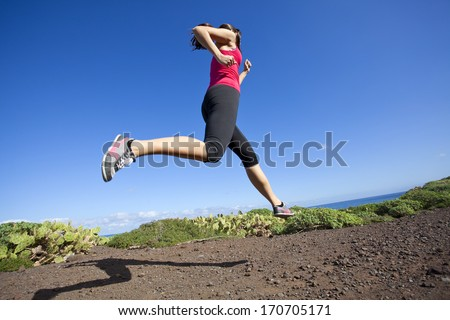 athlete woman running in nature. Healthy active lifestyle young woman exercising outdoors. - stock photo
