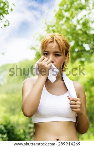 Athlete woman wiping sweat from her forehead with a towel after