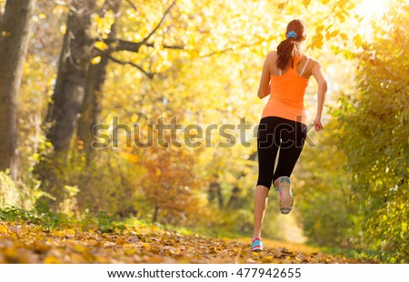 Athlete young woman running in morning sunrise training for marathon and fitness. Healthy active lifestyle in outdoor. Photographed from backside