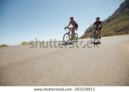 Athletes competing in the cycling leg of triathlon. Triathletes cycling on open country roads. Cyclist riding down hill. - stock photo