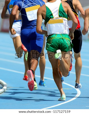 Athletes from back running on track during a competition - stock photo