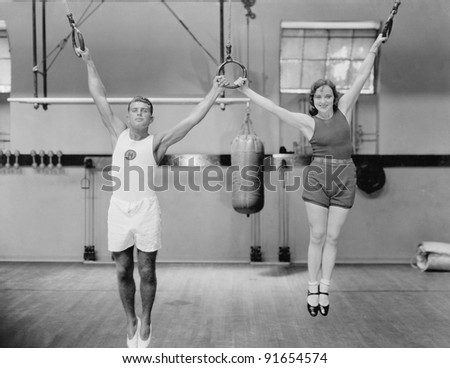 Athletes on rings in gym - stock photo