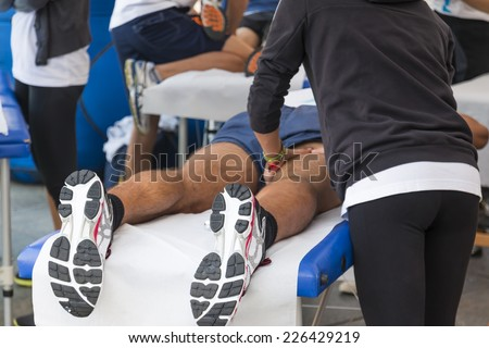 athletes relaxation massage before sport event, marathon muscles massage - stock photo
