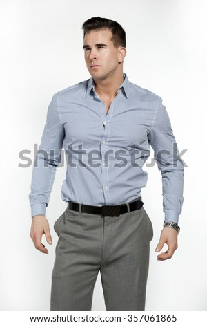 Athletic and attractive caucasian male wearing a fitted blue shirt and gray suit pants in a studio setting on a white background posing and looking to the left.