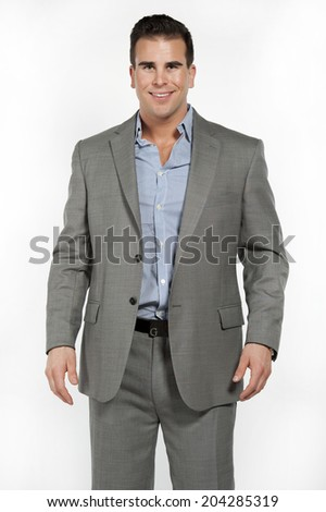 Athletic and attractive caucasian male wearing a fitted gray suit with a blue button down shirt in a studio setting on a white background posing and looking at the camera and smiling. - stock photo