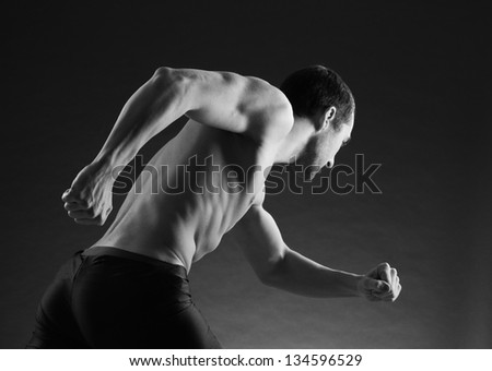 Athletic and muscular man is running - stock photo