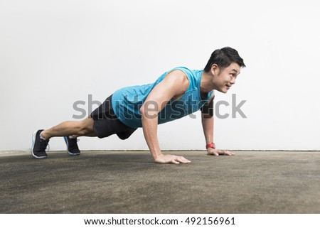 Athletic Asian man doing push up exercise. Action and healthy lifestyle concept.