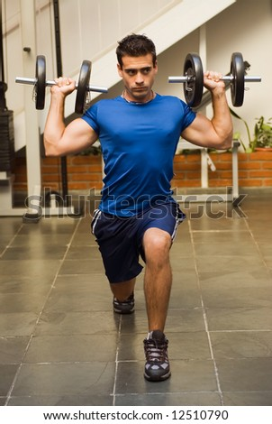 Athletic, attractive man doing lunges with dumbbells in a gym - stock photo