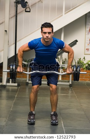 Athletic, attractive man executing a deadlift in a gym. Vertically framed shot. - stock photo