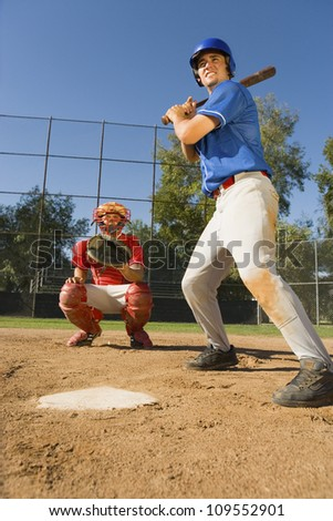 Athletic baseball player ready to hit the shot with catcher in background - stock photo
