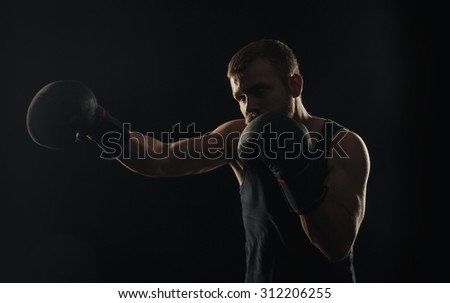 Athletic bearded boxer with gloves isolated on a dark background