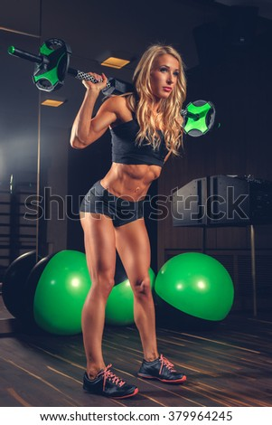 Athletic blond woman holding barbell in a gym.