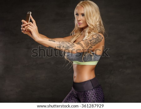 Athletic blond woman with tattoo on her arm taking picture by smartphone. - stock photo