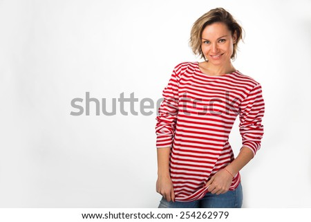 Athletic blonde in a red striped sweater, posing in studio on white background. A girl shows off her sexy tummy. Abdominal muscles, healthy lifestyle, women's fitness. - stock photo