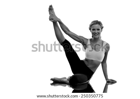 Athletic blonde sitting on floor stretching leg up smiling at camera against mirror - stock photo