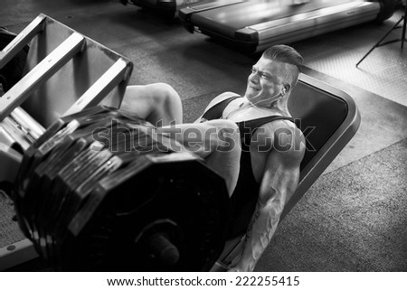 Athletic bodybuilding man in gym leg lifting weight - stock photo