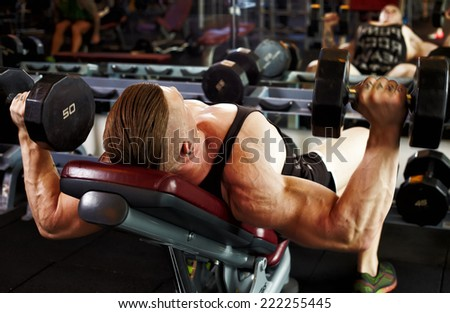 Athletic bodybuilding man in gym working with gantels - stock photo