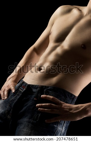 Athletic built young man with well-defined abdominal and pectoral muscles isolated on a black background