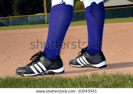 Athletic cleats are planted firmly in the dirt of the baseball field.  Purple socks.