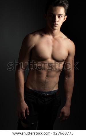 Athletic confident guy. Low key - stock photo