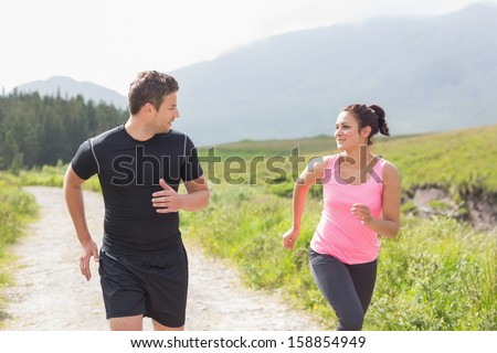 Athletic couple on a jog through the countryside - stock photo