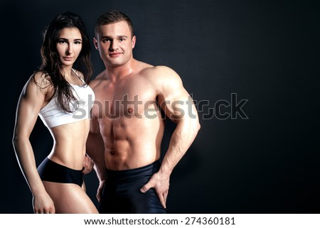Athletic couple posing in studio. Man and woman with muscle body. - stock photo