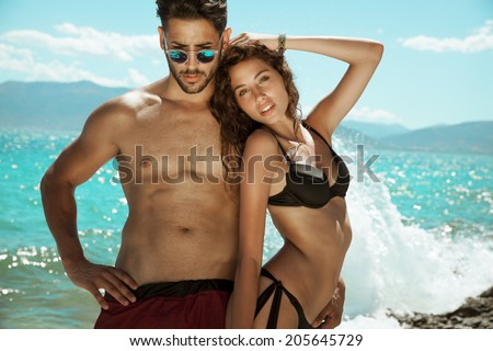 Athletic couple smiling at camera and embracing on the beach.Toned in warm colors. outdoors shot on the beach. - stock photo