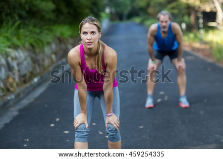 Athletic couple taking a break after jogging on the open road